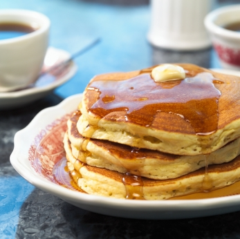 Homemade pancakes with maple syrup on restaurant ware china