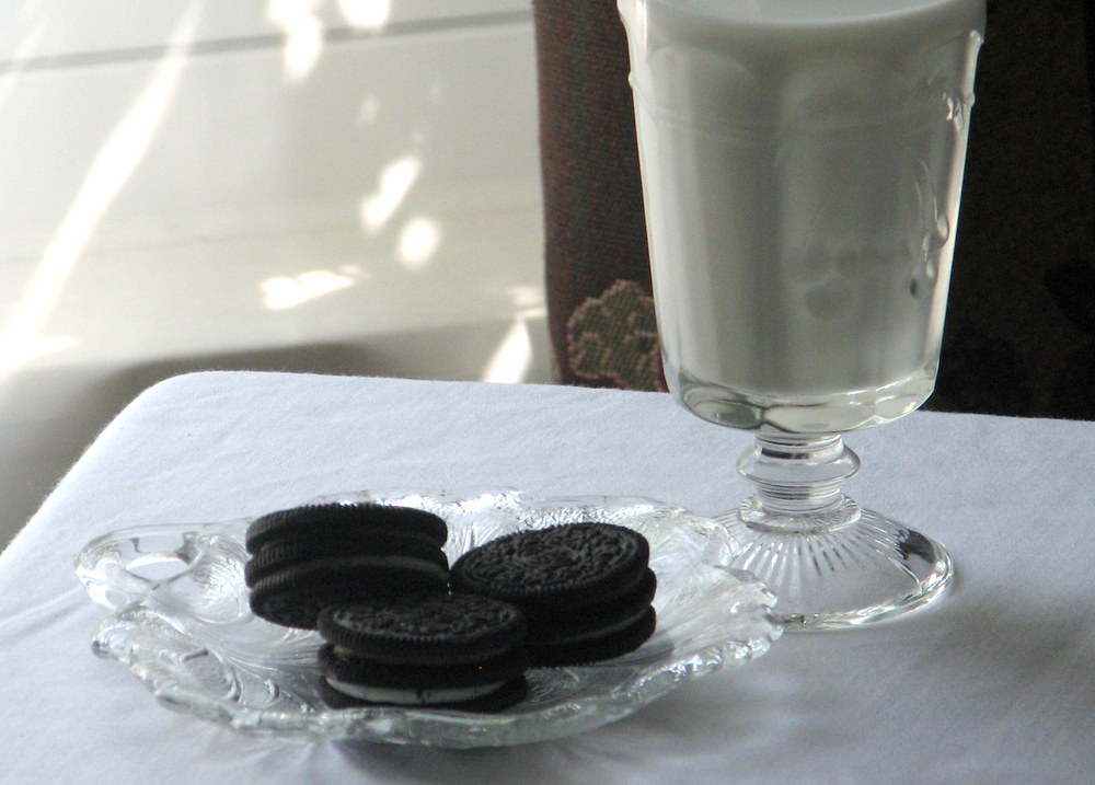 Vintage glass dish of Oreo cookies and milk